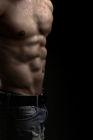 bare chest: Closeup view of one handsome strong young male bare chest of muscular body standing posing on studio background, vertical picture
