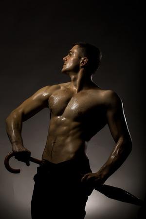 nackte brust: Junger stattlicher Mann mit muskulösen Körper nass nackte Brust und Rumpf posiert im Studio Regenschirm auf grauem Hintergrund Lizenzfreie Bilder