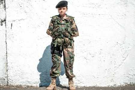 standoff: Little girl soldier with strict serious face in camouflage and black beret on her head standing on white wall background with hands on back