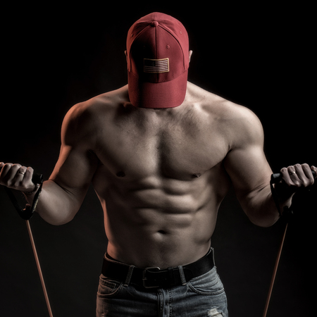 training device: One strong young man with muscular body in red sport  cap standing posing holding training device in studio on black background, square picture
