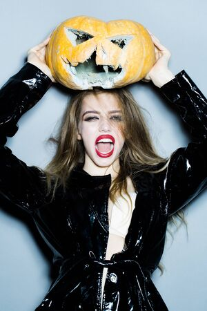 leather coat: Young sexy woman with bright glamour makeup on pretty emotional face and beautiful hair in black leather coat holding scary halloween pumpkin on grey background