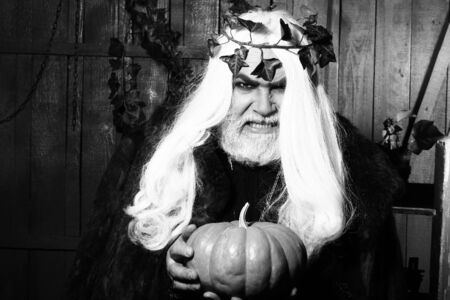 sorcery: Evil wizard with long hair and beard in wreath of ivy with pumpkin in old wooden house, black and white
