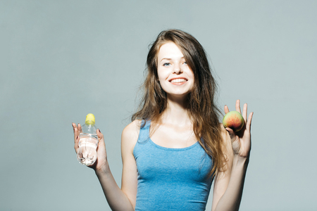 undershirt: Beautiful girl with long hair in blue undershirt holds water bottle apple and smiles on grey wall Stock Photo