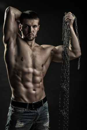 One handsome strong young man with muscular body in blue jeans holding rope in hands standing posing in studio on black background, vertical picture
