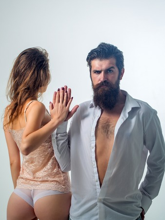 man ass: couple of handsome bearded man with long beard and moustache on serious face near young pretty girl with sexy body and buttocks in lingerie in studio isolated on white background
