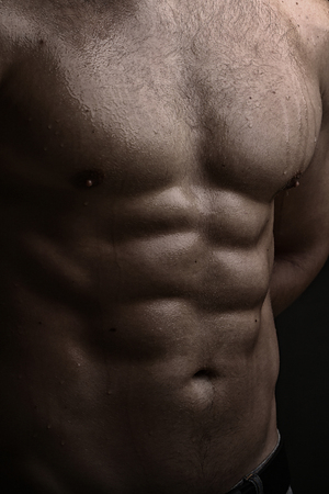 nackte brust: Closeup view of one handsome strong young male bare chest of muscular wet body standing posing on studio background, vertical picture