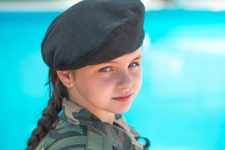 army face: Young girl child with pretty serious face brunette in army ammunition black beret on blue background outdoor