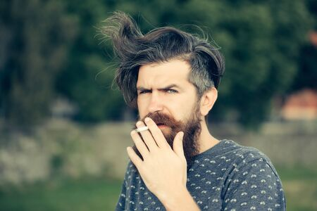 hairy closeup: handsome sexy bearded young man hipster with long beard and mustache has stylish hair on serious hairy face smoking cigarette outdoor on green natural background, closeup