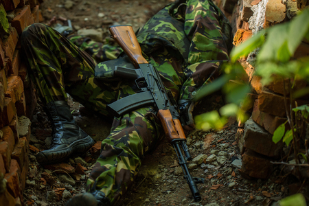 standoff: Dead body of killed soldier in war dressed in military ammunition laying on ground with rifle outdoor Stock Photo