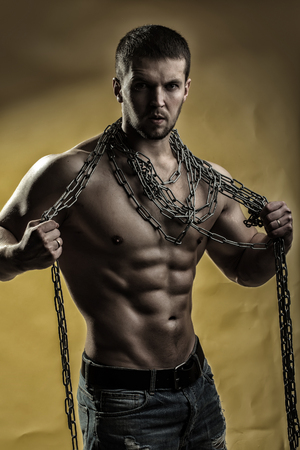 pectoral muscle: One handsome strong young man with muscular body in blue jeans holding rope with hands hanging on neck and shoulders standing posing in studio on yellow background, vertical picture