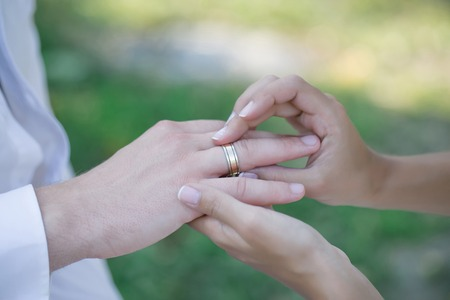 puts: Hands of bride puts gold ring on groom finger during wedding ceremony on natural background