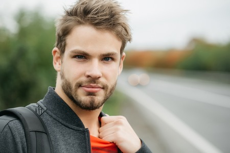 brown hair blue eyes: Young boy with cool fashion beard on handsome serious face blue eyes brown hair in black and red clothes outdoor on road way background