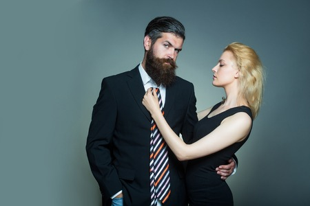 long beard: young fashionable couple of woman with pretty face and blonde hair and handsome bearded man with long beard in black jacket and tie in studio on grey background Stock Photo