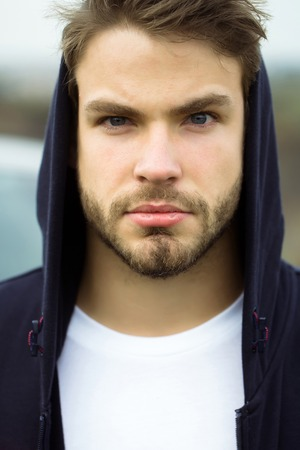 Young man with bearded serious face brown hair and blue eyes in casual dark hood on head and white t shirt outdoor Фото со стока