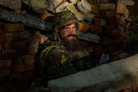standoff: Man soldier with dust grime beard and angry on his face in helmet and war camouflage and rifle in his hands sitting in brick stone ruins Stock Photo