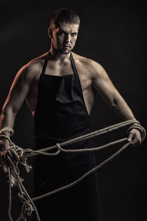 sexual anatomy: One handsome strong young man with muscular body in working blue apron holding rope standing posing in studio on black background, vertical picture