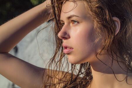 wet lips: Young girl with pretty serious face sexy lips wet brown hair and healthy skin holding her head by hand