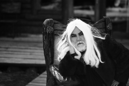 house coat: Old bearded man wizard with long hair and beard in fur coat sits in wooden chair on log house background, black and white