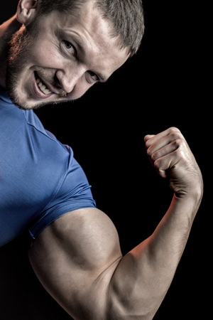 sexual anatomy: One strong smiling young man with muscular body in blue sport shirt showing big biceps on hand standing on studio black background, vertical picture Stock Photo