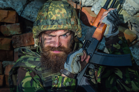 aggressiveness: Soldier man with young bearded wicked angry dirty face in military helmet on head and rifle in hands wearing army ammunition sitting in stone brick ruins Stock Photo