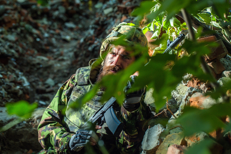 standoff: Young soldier with sad bearded face in military helmet and camouflage with gun on ruined bricks background in forest