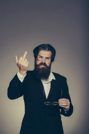 gives: Rude man bearded hipster male in suit with vintage glasses gives middle finger on grey wall