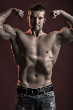 pectoral muscle: One strong young man with muscular body in jeans looking forward standing posing in studio on red background, vertical picture Stock Photo