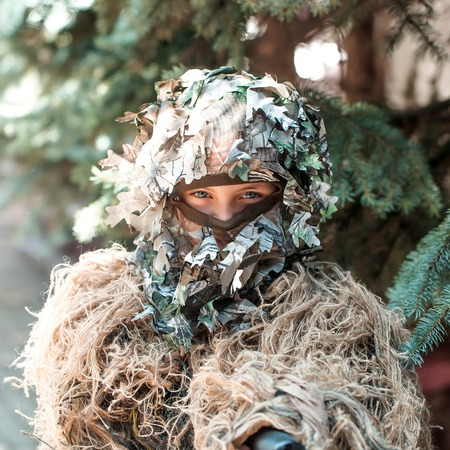 standoff: Young girl soldier defender with blue eyes face closed by mask in ghillie camouflage military ammunition with gun standing on background of spruce tree