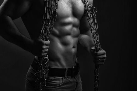 sexual anatomy: One handsome strong young man with muscular body in blue jeans holding rope with hands hanging on neck and shoulders standing posing in studio black and white, horizontal picture