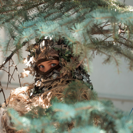 aggressiveness: Young girl soldier defender with blue eyes face closed by mask in ghillie camouflage military ammunition with gun standing on background of spruce tree