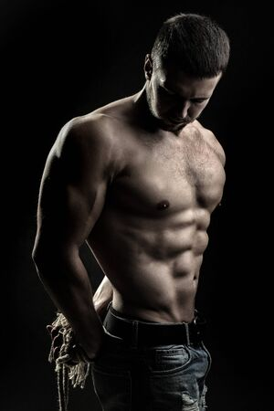 sexual anatomy: One handsome sexual strong young man with muscular body in blue jeans with tied hands by rope standing in studio on black background, vertical picture