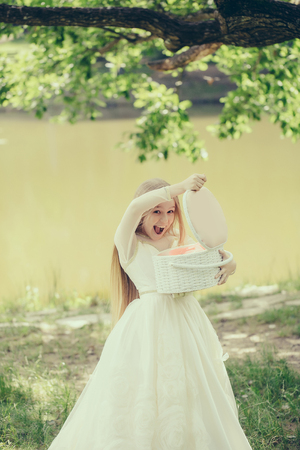 prom queen: small girl kid with long blonde hair and pretty smiling happy face in prom princess white dress standing sunny day outdoor near water with basket Stock Photo