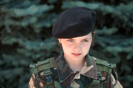 aggressiveness: Young girl child soldier with serious pretty face brunette in army camouflage black beret on head on natural background outdoor