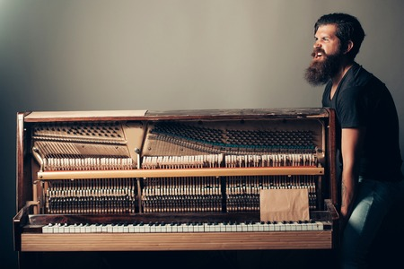 pianoforte: handsome bearded strong man with stylish hair mustache and beard trying to move old wooden or wood open piano with keyboard on grey background, copy space