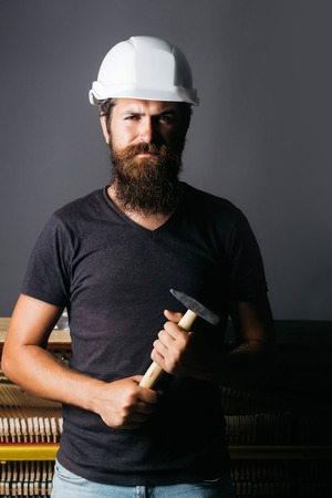 grand hard: handsome bearded man worker with beard in building helmet or hard hat holds hammer near wooden or wood piano on grey background Stock Photo