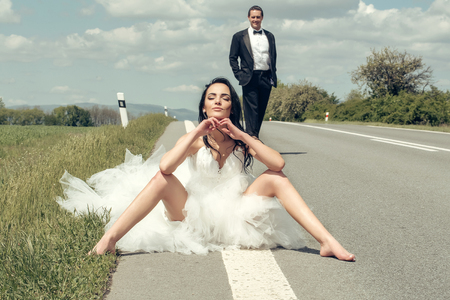 young wedding happy couple of sexy girl with brunette hair and pretty face in white bride dress and handsome man in black groom suit on road way on cloudy blue sky nature background