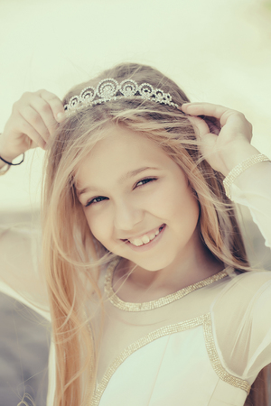 prom queen: small girl kid with long blonde hair and pretty smiling happy face in dress and prom princess crown standing on white background, closeup