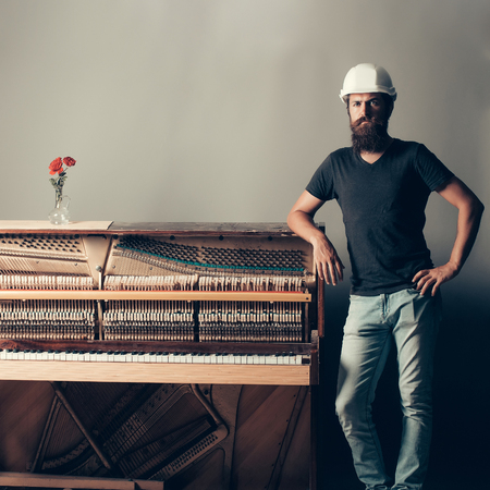 pianoforte: handsome bearded man with mustache and beard in building helmet or hard hat near old wooden or wood open piano with keyboard and glass vase with red rose flowers on grey background, copy space Stock Photo