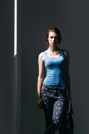 undershirt: Attractive young woman in blue undershirt and jeans poses in light in studio on grey wall