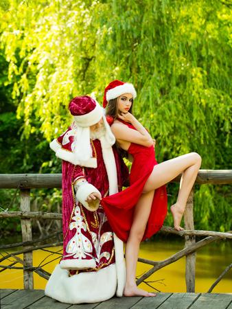 Lustige Weihnachtsmann-Mann im neuen Jahr Weihnachten roten Kostüm mit hübschen Mädchen in sexy Kleid auf natürlichen Hintergrund