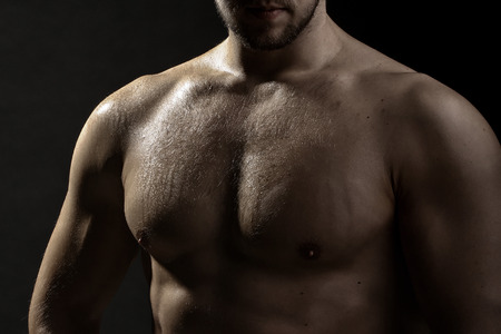 sexual anatomy: Closeup view of one handsome sexual strong young male bare chest of muscular wet body standing posing on studio background, horizontal picture