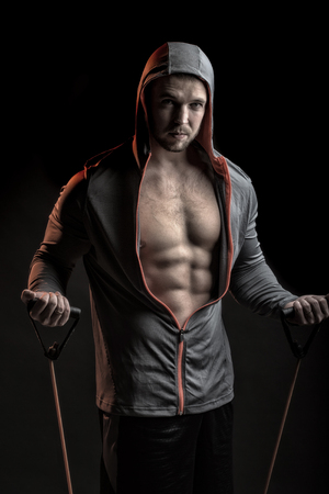 training device: One sexual strong young man with muscular body in grey sport jacket with hood holding training device standing on studio black background, vertical picture