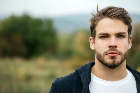 brown hair blue eyes: Young guy with bearded handsome sexy serious face blue eyes brown hair in dark hoody posing outdoor on natural background