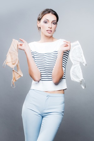 face cloth: young stylish woman or girl with glamour makeup on pretty face in striped fashionable cloth on slim sexy body choosing bra in wardrobe posing in studio on grey backgroud
