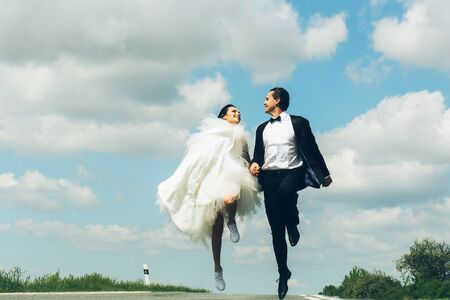 young wedding happy couple of girl with brunette hair and pretty face in white bride dress and handsome man in black groom suit running on road way on cloudy blue sky nature background Stock Photo