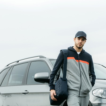 hoody: Young guy with beard on his serious face in casual hoody dark blue baseball cap on head and sports bag posing on background of gray car outdoor