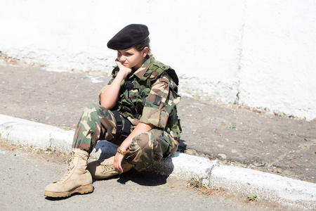 army face: Young girl child with pretty sad thoughtful face in army camouflage ammunition and black beret sitting on stone ground outdoor Stock Photo