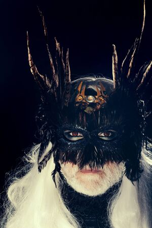 hair feathers: Male bearded face with long white hair and ominous sight in vintage decorative masque with dark brown feathers for fancy ball on black background studio Stock Photo