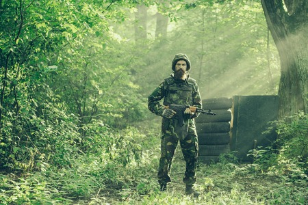 standoff: Young soldier bearded man in military camouflage and helmet with rifle in hands standing on post on background of green trees of forest and sun beams