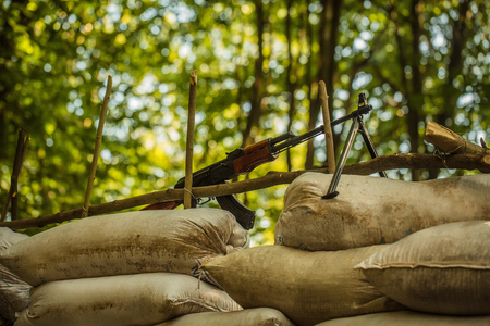 aggressiveness: Military rifle standing on sandbags block post in forest on background of green trees